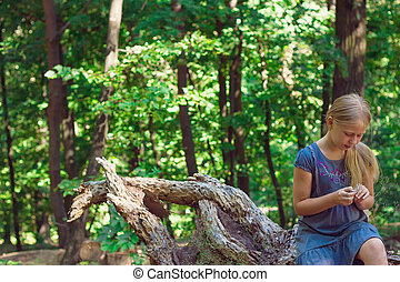 Girl sitting on a tree stump
