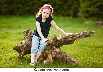 Girl sitting on a tree trunk
