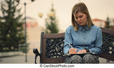 Girl sitting on a wooden bench, writes a notebook, outdoors