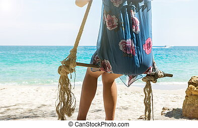 Girl sitting on a wooden swing on the beach