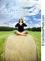 Girl sitting on bale of straw