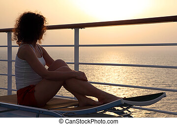 girl sitting on beach chair at ship deck and looking into...