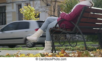 Girl sitting on bench outside on a sunny autumn day