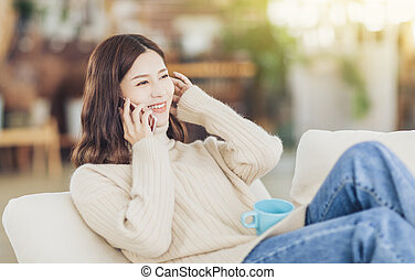 girl sitting on couch with cup of coffee, tea and talking on the phone