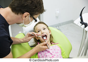 Girl sitting on dental chair on her regular dental checkup -...