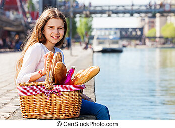 Girl sitting on embankment with picnic basket