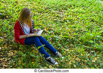 Girl sitting on grass and reading a book