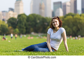 Girl sitting on green grass