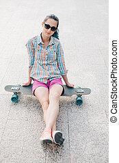 Girl sitting on longboard.
