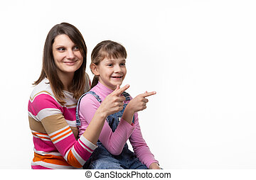 Girl sitting on moms lap and joyfully point a finger to an empty place