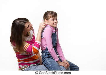 Girl sitting on moms lap, mom fun tugs at the girls ear