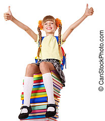 Girl sitting on pile of books showing thumbs up.