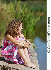 Girl Sitting On Rock While Looking Away By Lake