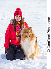 Girl sitting on snow with collie dog