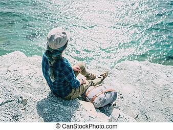 Girl sitting on steep coast