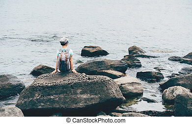 Girl sitting on stone in the sea