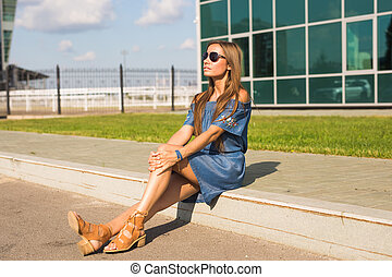 Girl sitting on street in summer day