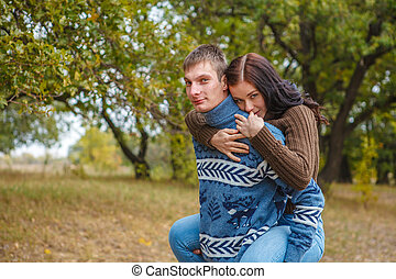 girl sitting on the back of a guy. A couple in love in the park