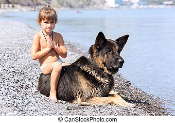 girl sitting on the bank with a dog
