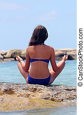 girl sitting on the beach in a lotus position