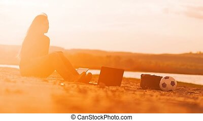girl sitting on the beach with a laptop Slow motion video