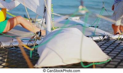 girl sitting on the board of sailing catamaran