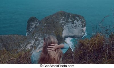 Girl sitting on the cliff and admiring amazing view in Nusa Penida