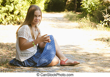 girl sitting on the dirt road