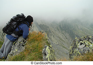Girl sitting on the edge of a mount