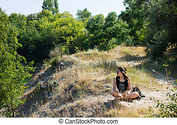 Girl sitting on the edge of the cliff