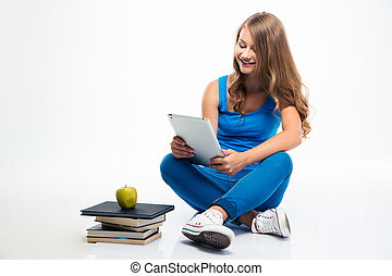 Girl sitting on the floor and using tablet computer