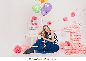 girl sitting on the floor holding colored balloons on a white background. Beautiful woman on holiday