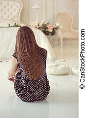 Girl sitting on the floor in bedroom