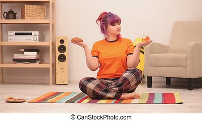 Girl sitting on the floor with healthy and unhealthy food in hands. Difficult choice of a croissant or an apple. Overweight Concept. Healthy food concept. Prores 422.