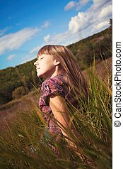 girl sitting on the green grass