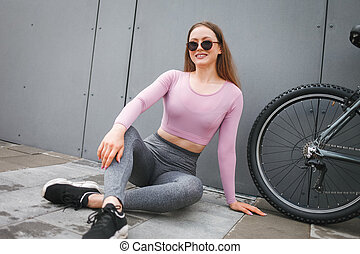Girl sitting on the ground after riding a bike