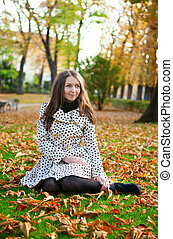 Girl sitting on the ground in park on a fall day