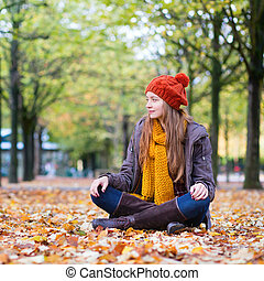 Girl sitting on the ground on a fall day
