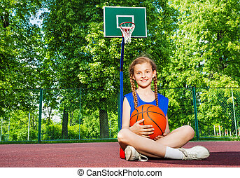 Girl sitting on the playground with ball