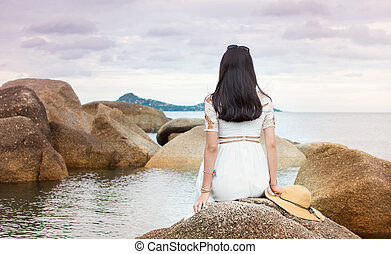 Girl sitting on the seaside rocks