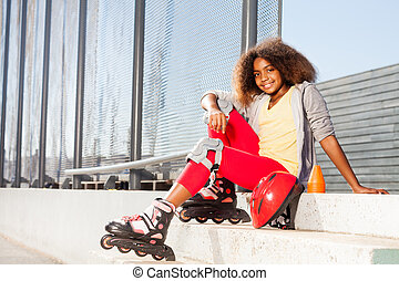 Girl sitting on the stairs in roller skates