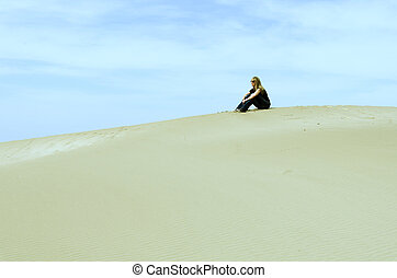 girl sitting on top of a dune looking landscape