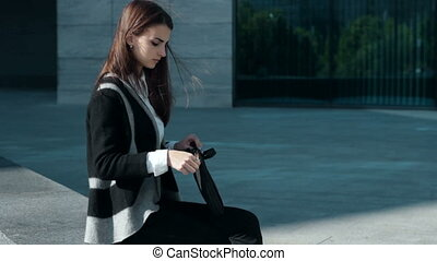 girl sitting outdoors in the wind and works with mobile tablet
