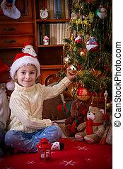 Girl sitting under Christmas tree holding ball