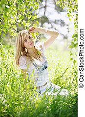 girl sitting under the birch