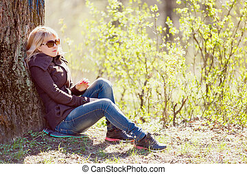 girl sitting under the tree in a autumn forest