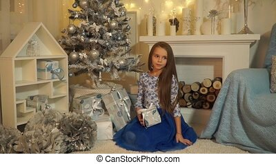 Girl sitting under the tree near the fireplace with a gift in their hands