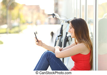 Girl sitting using a mobile phone in a park