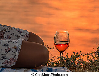 girl sitting with a glass of wine at sunset, a young woman enjoying evening, close up