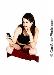 Girl sitting with cell phone.